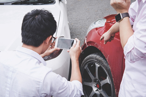 person taking photo of car accident